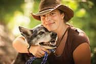 Jen-Osha Buysse sitting with a dog
