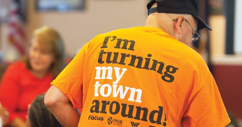 """Man in a bright orange t-shirt that reads """"I'm turning my town around"""" on the back"""