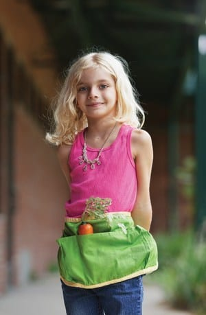 Girl enjoying local produce wearing an apron with a carrot in the pocket