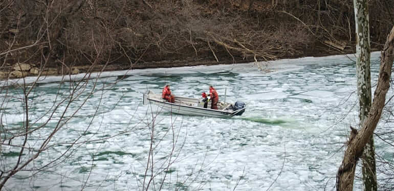 Three men wearing life vests on a motorboat on an ice covered river