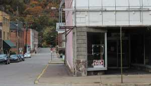 """abandoned looking store with sign reading """"for sale by owner"""""""