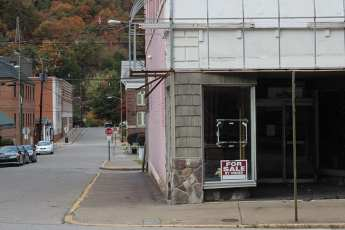"abandoned looking store with sign reading ""for sale by owner"""