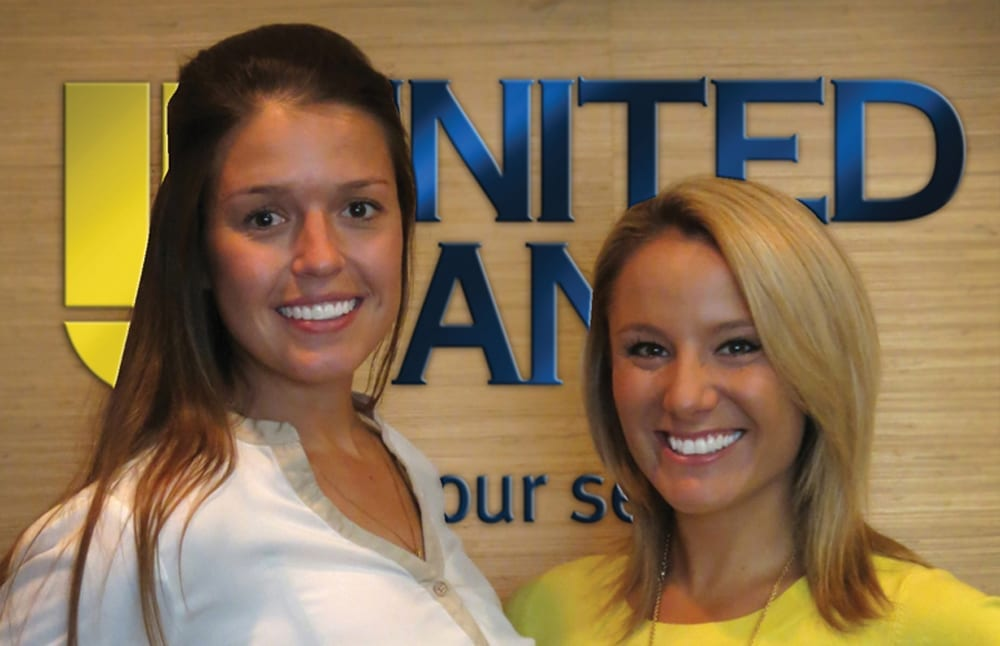 Abby Monson and Blair Trout pose in front of the United Bank sign