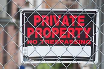 """Sign hooked behind a fence that reads """" Private Property No Trespassing"""""""