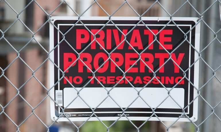 "Sign hooked behind a fence that reads "" Private Property No Trespassing"""