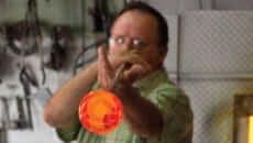 Glassblower blowing glass