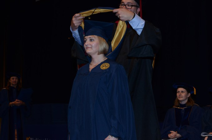 Chad Mazera places my hood during the WVU Reed College of Media commencement