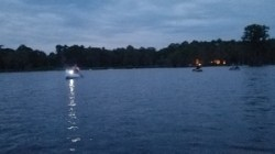 Paddlers and the lights of Banks Lake Outpost behind them 31.0325352, -83.0984963