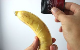 someone holding a banana with a condom over it demonstrating usage