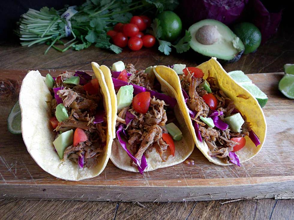 Slow Cooker Carnitas Tacos with a cilantro-lime sauce! Super easy way to feed a crowd!
