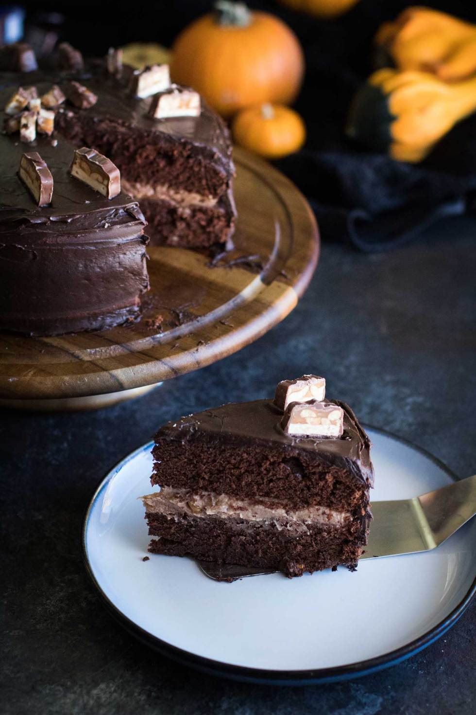 Snickers Cake - A rich chocolate cake with a melted down snickers filling and buttercream frosting. The perfect solution to leftover halloween candy.