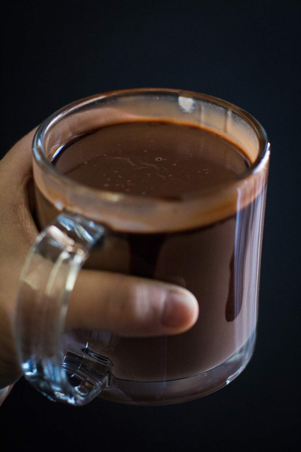 Close-up of person holding thick hot chocolate in a glass mug.