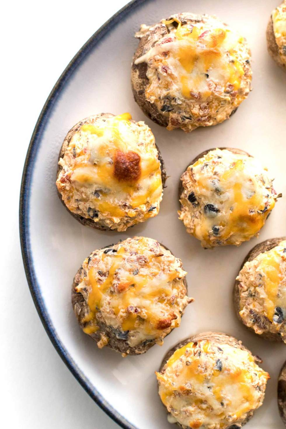 Overhead photo of stuffed mushrooms with browned cheese on top.
