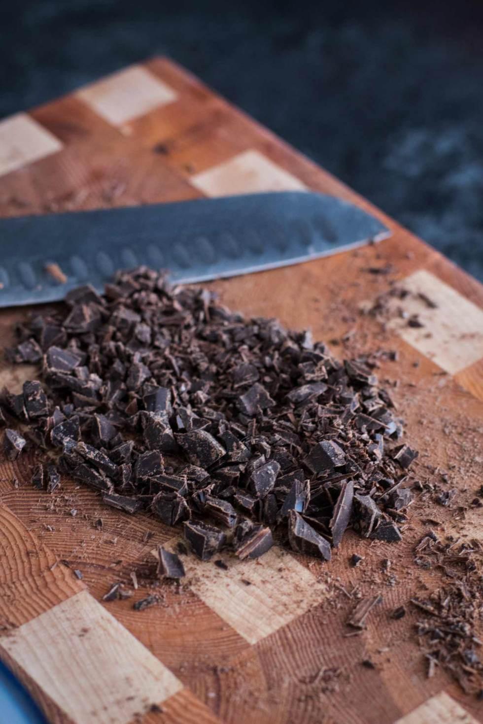 Chopped dark chocolate on a wood cutting board