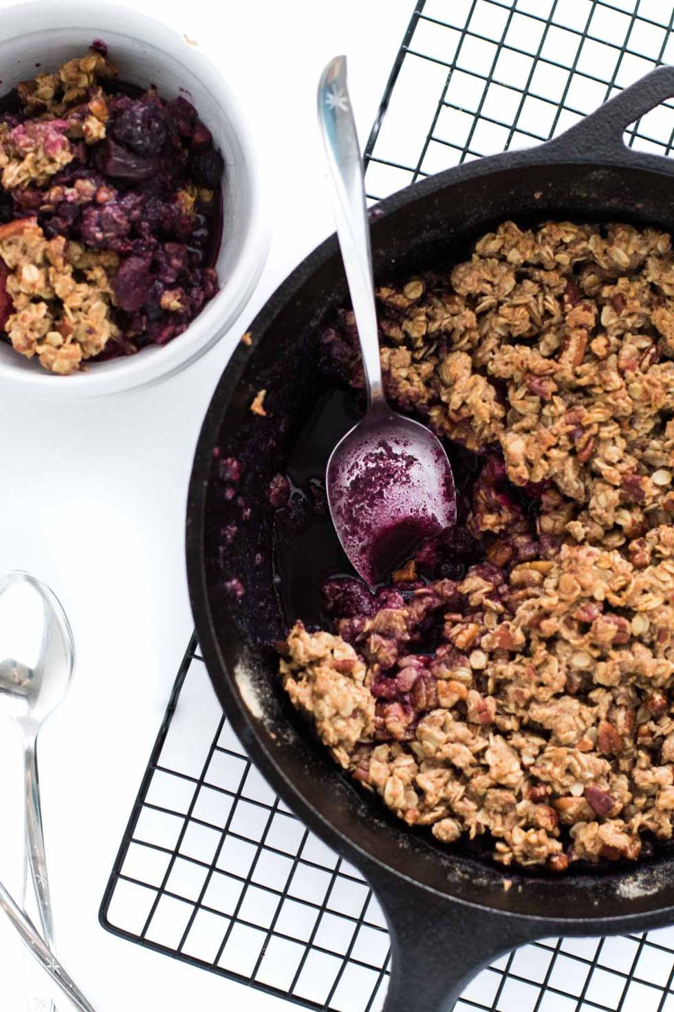 Closeup of cooked fruit crumble with a serving spoon sitting in the berry juice.