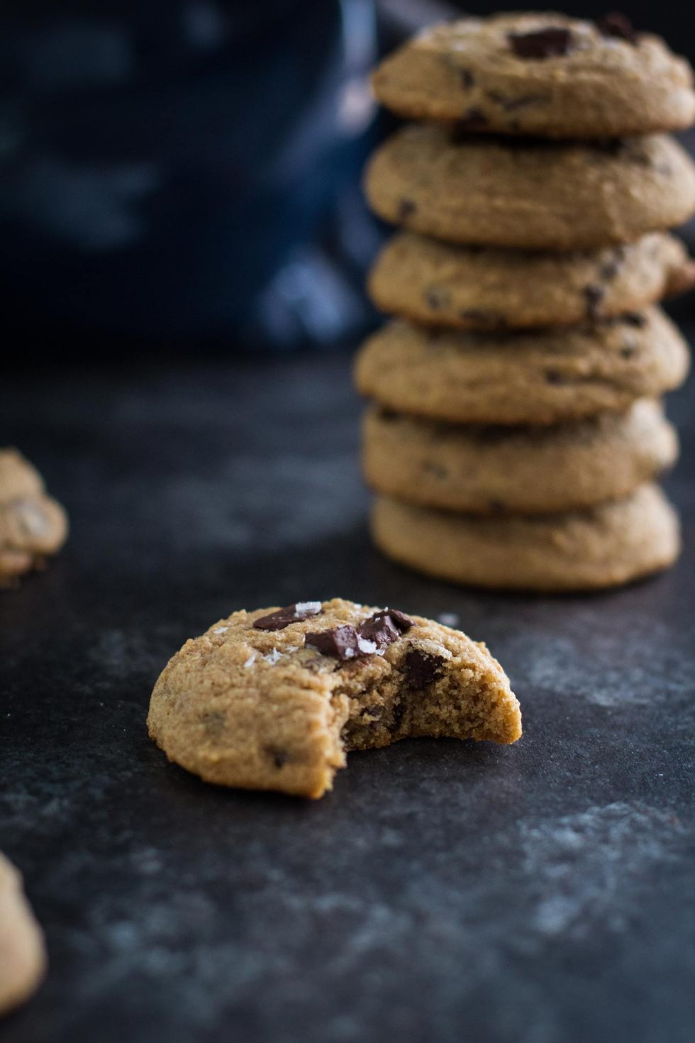 Close-up of whole wheat cookie with a bite out of it and a stack of cookies behind it