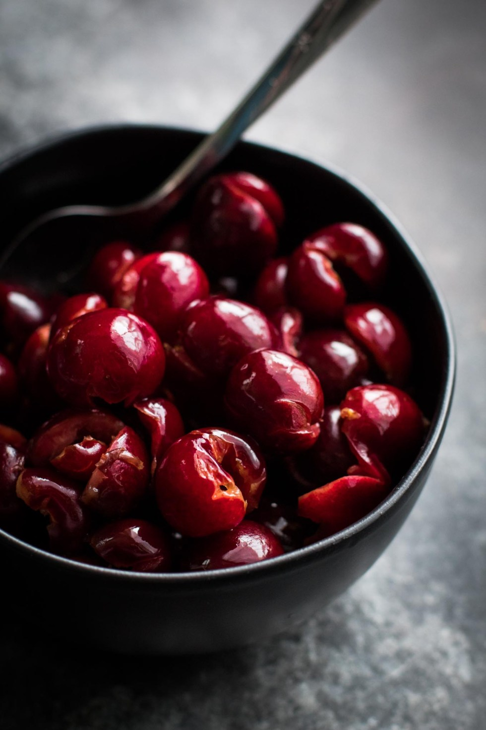 Black bowl of bourbon-soaked cherries