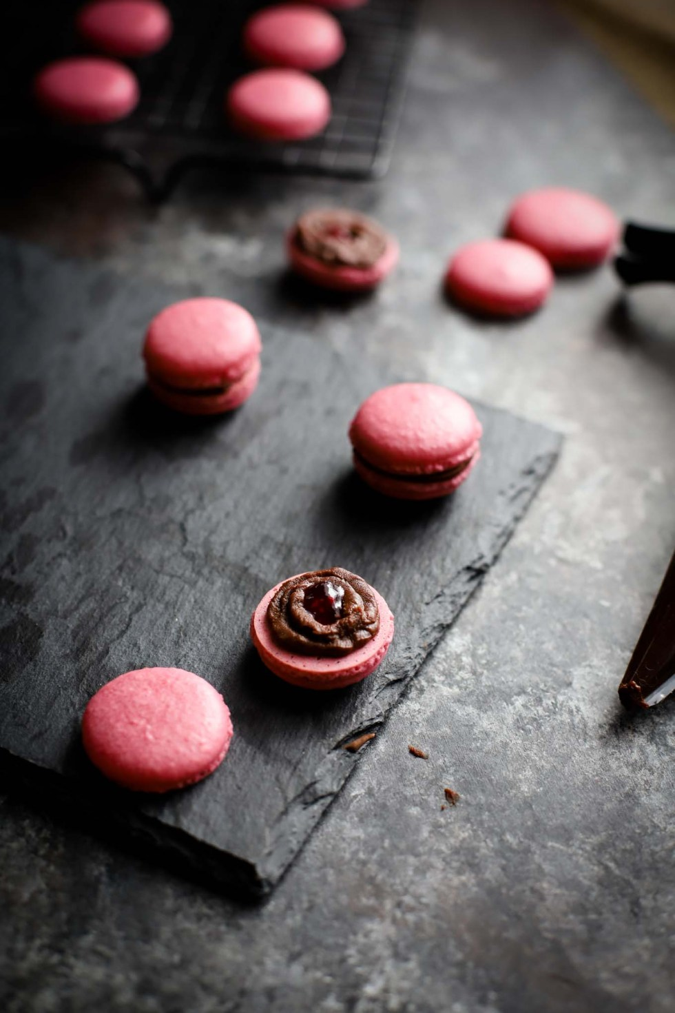 A photo of half a macaron topped with a ring of chocolate ganache and dab of raspberry jam in the middle.