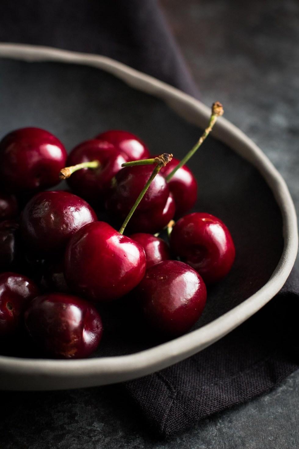 Fresh cherries in a black ceramic bowl