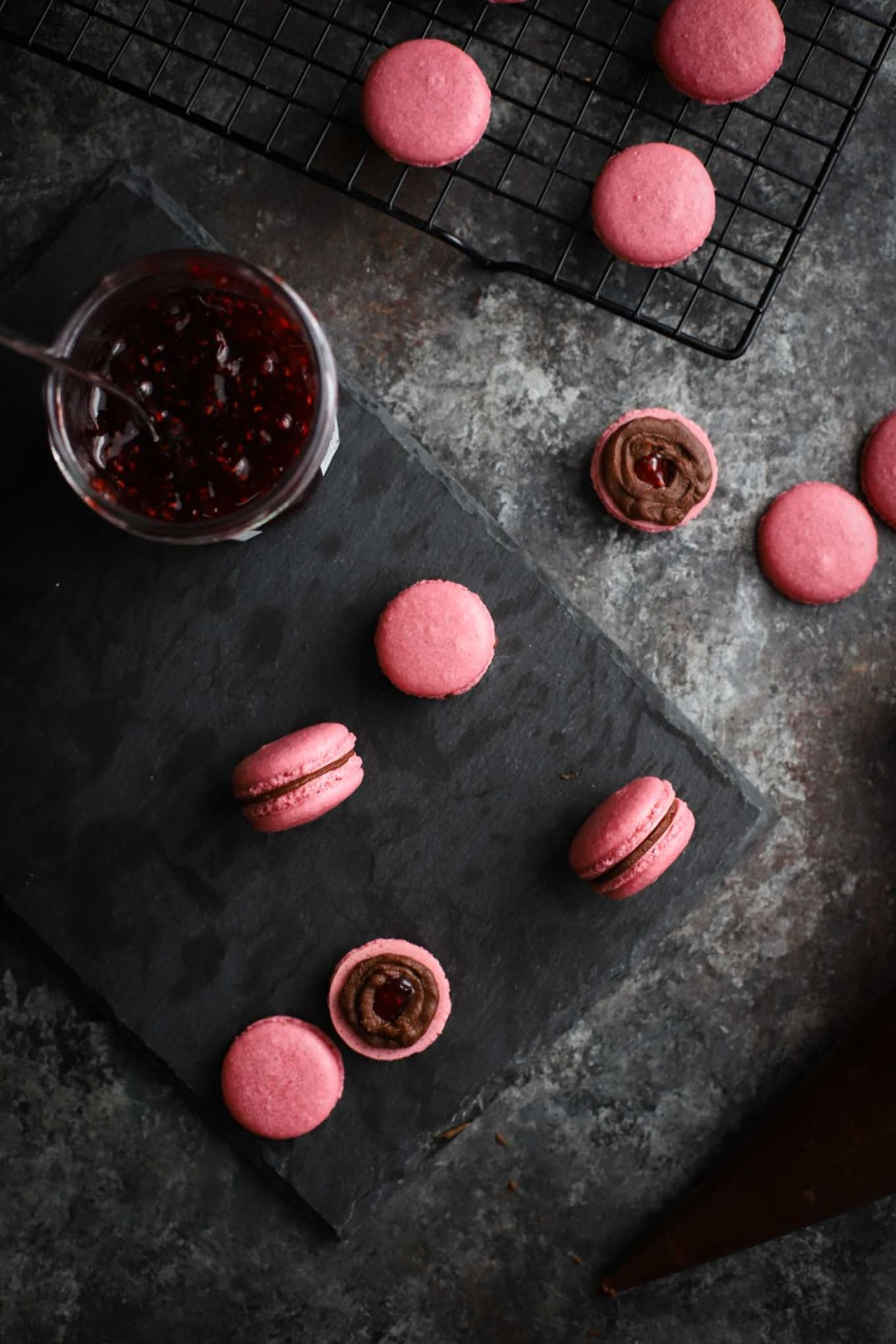 Overhead photo of hot pink macarons and half a macaron topped with chocolate ganache