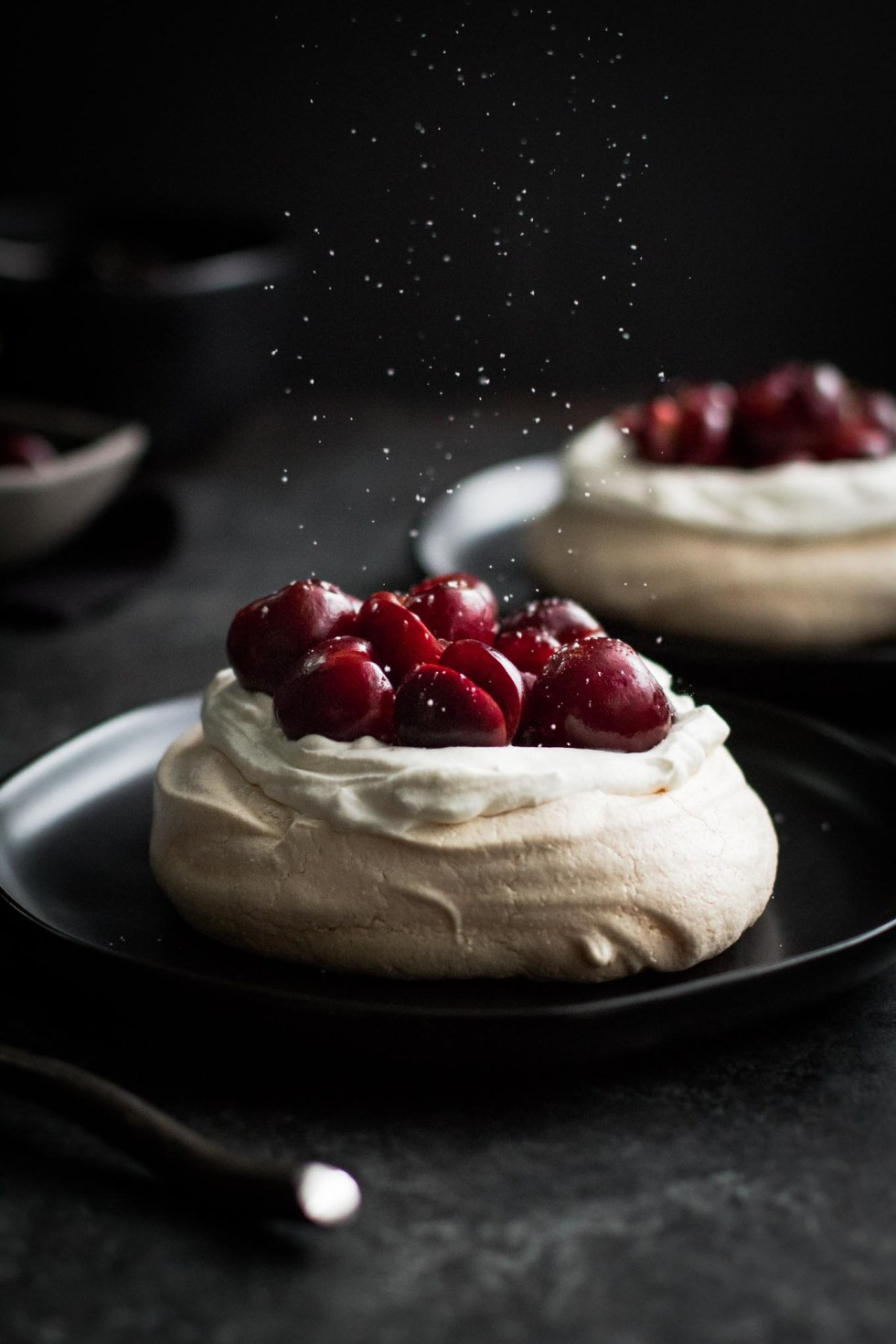 Two servings of pavlova with whipped cream and bourbon-soaked cherries