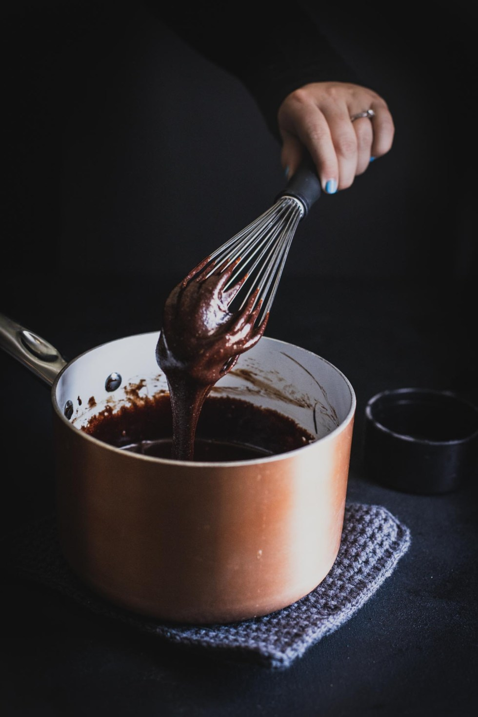 Whisking brownie batter in a copper saucepan