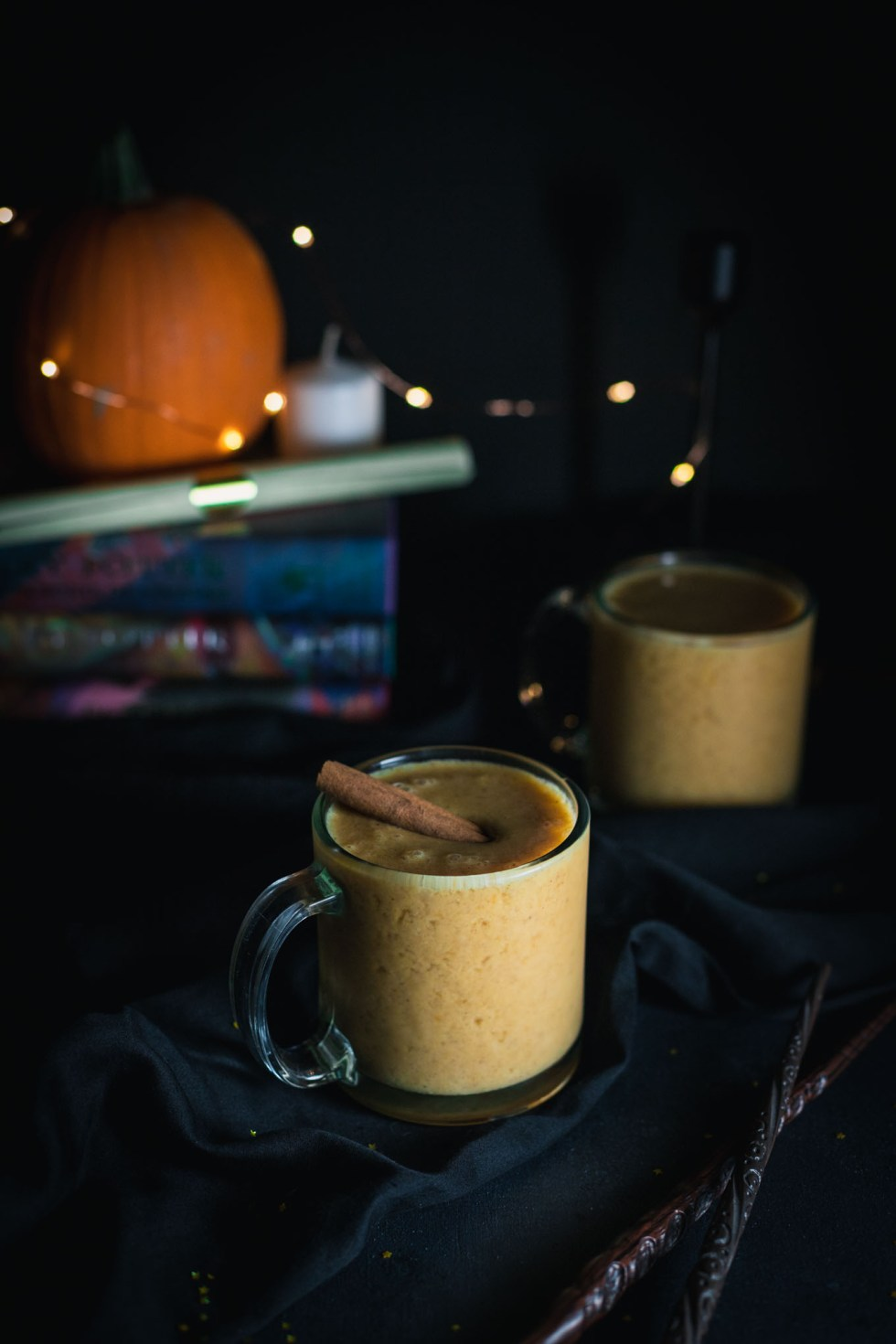 Harry Potter-inspired frozen pumpkin juice in glass mugs with cinnamon stick garnishes