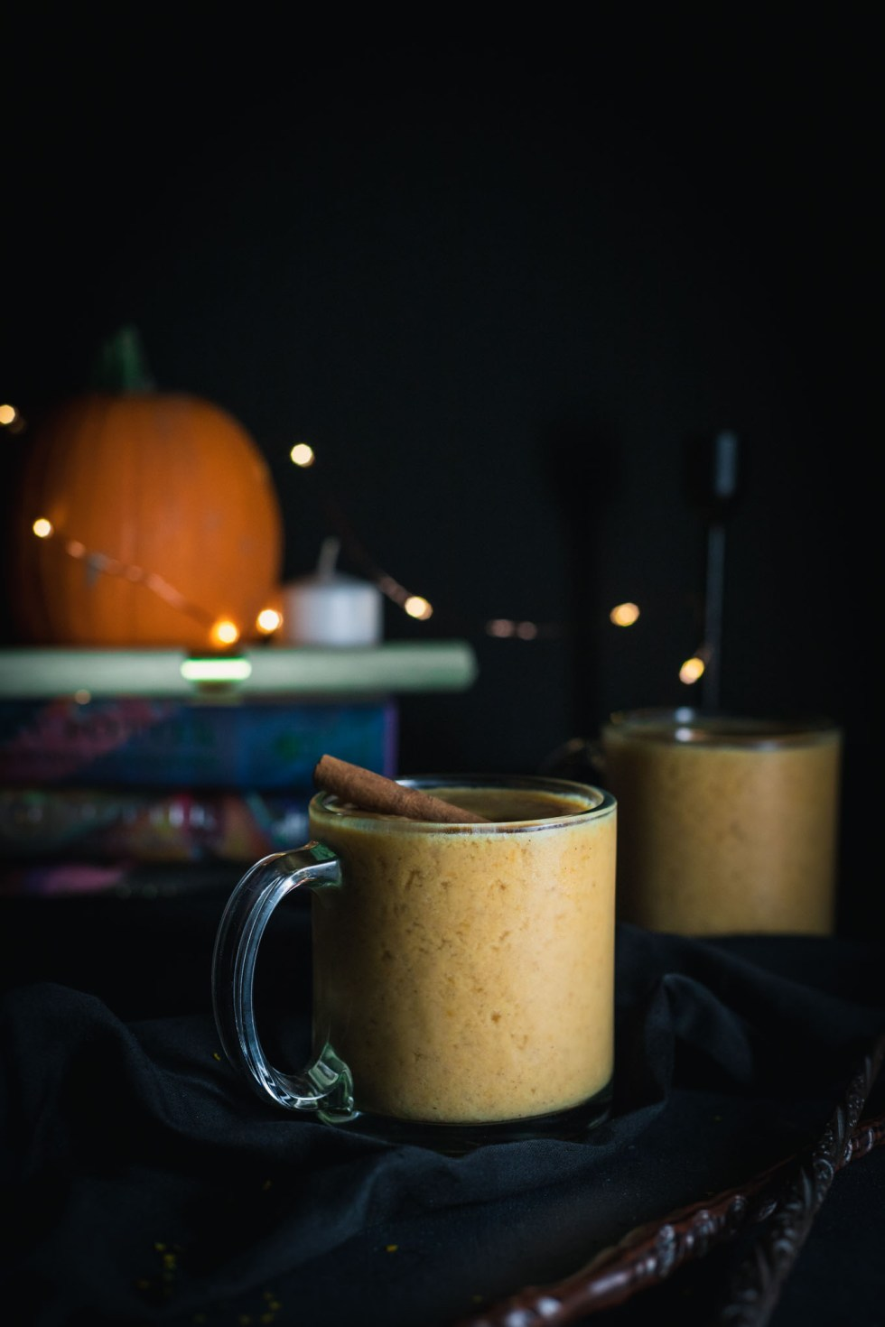 Two glass mugs filled with harry potter-inspired pumpkin juice with orange twinkly lights in the background