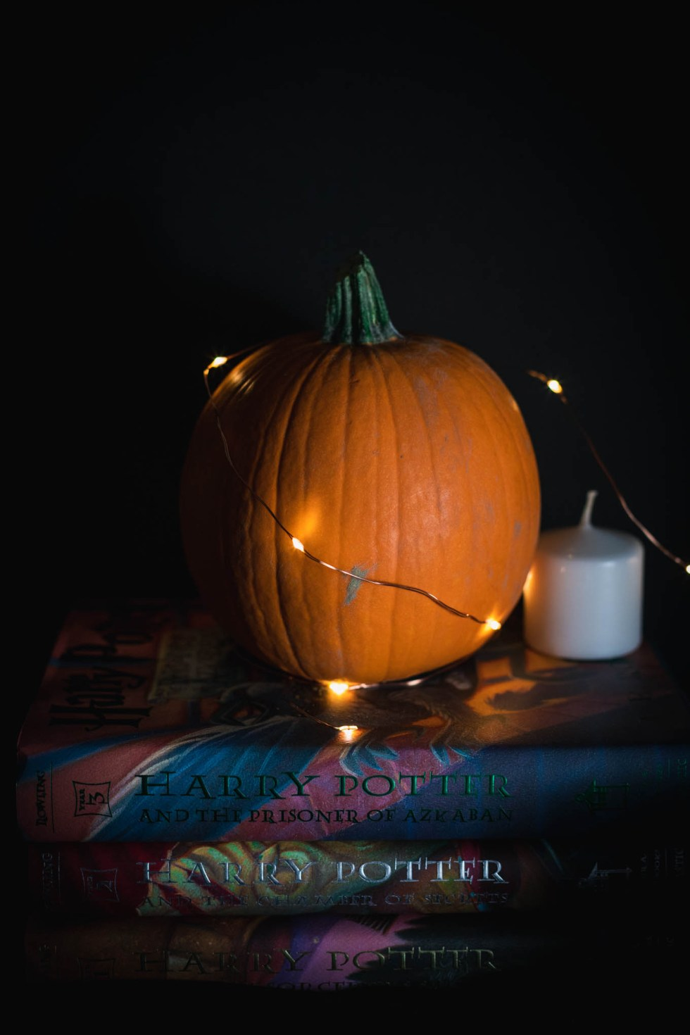Pumpkin and orange twinkly lights stacked on top of Harry Potter books