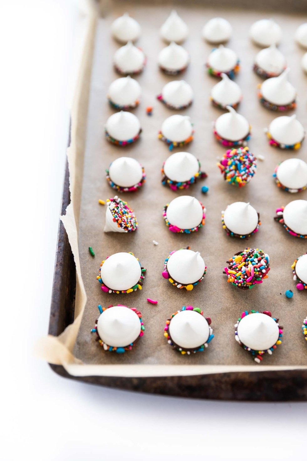 White meringue kisses covered in chocolate and sprinkles with a few tipped over to show their sprinkle casing.