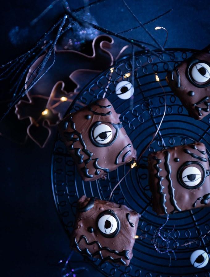 Brownies decorated like Hocus Pocus spellbooks cooling on a black wire rack.