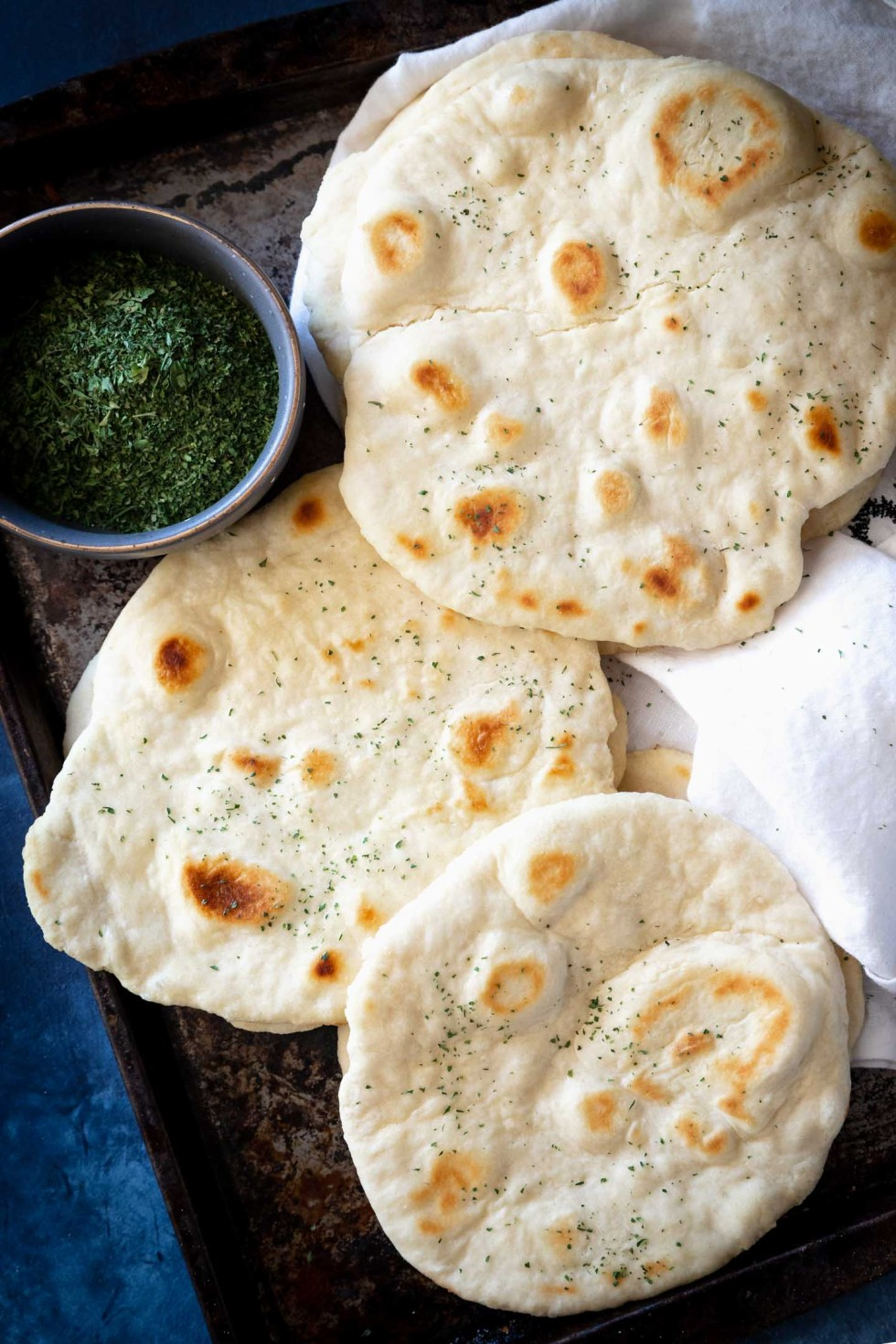 overhead view of several flatbreads laying on a baking sheet