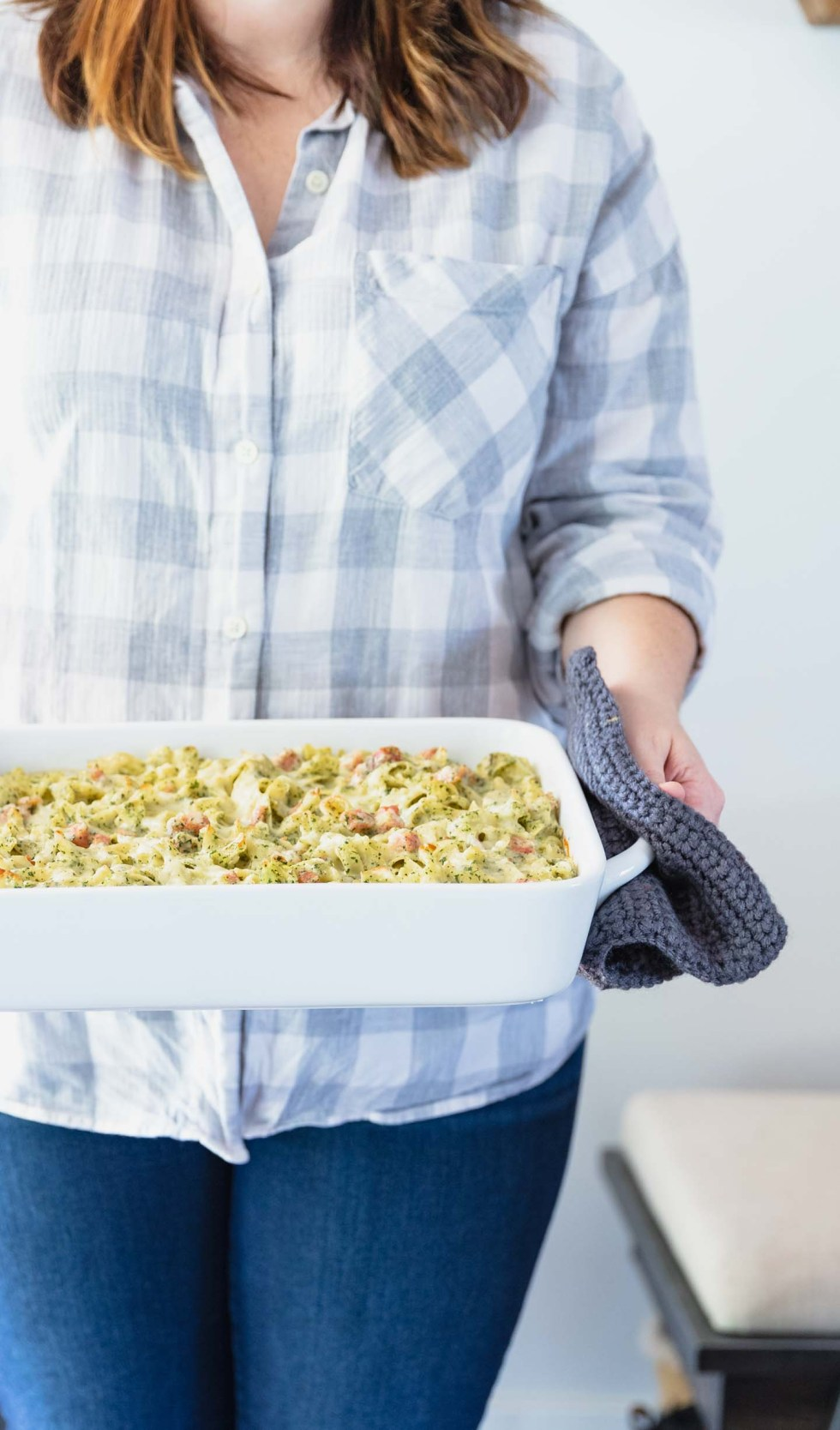 Girl in white flannel holding a ham noodle casserole dish