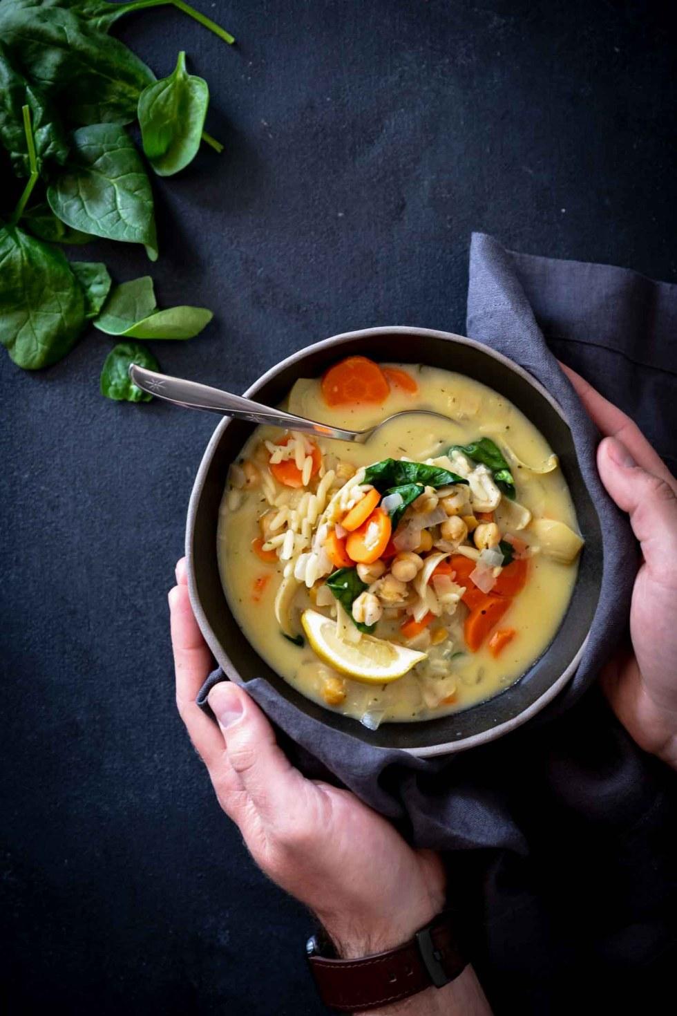 Dark black bowl filled with lemon artichoke orzo soup