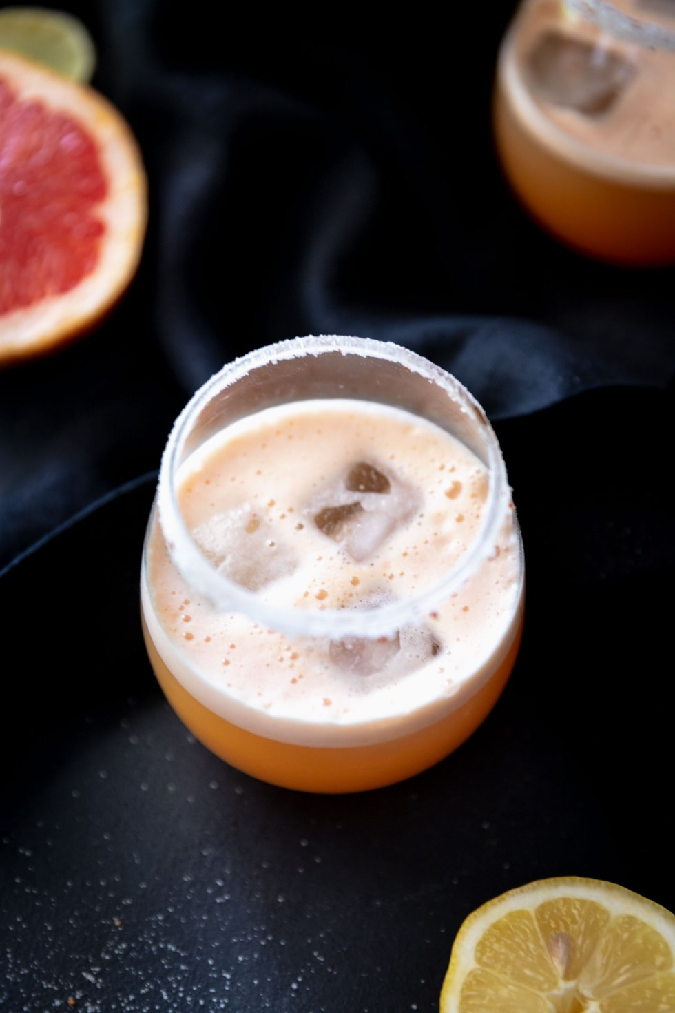 Stemless wine glass filled with grapefruit margarita and square ice cubes