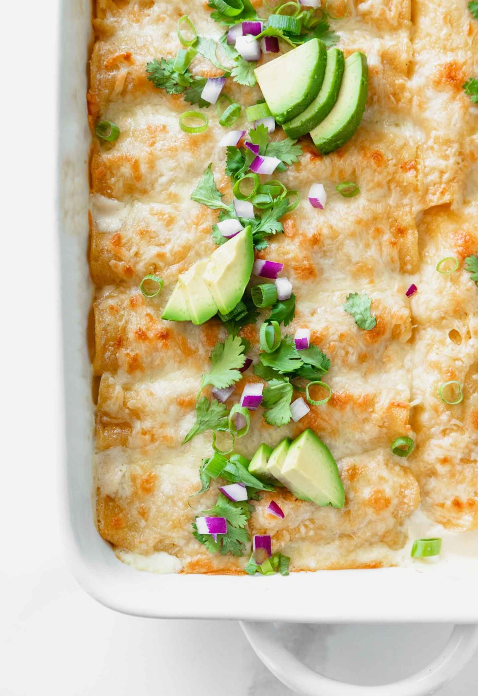 Overhead shot of white chicken enchiladas with avocado and green onion