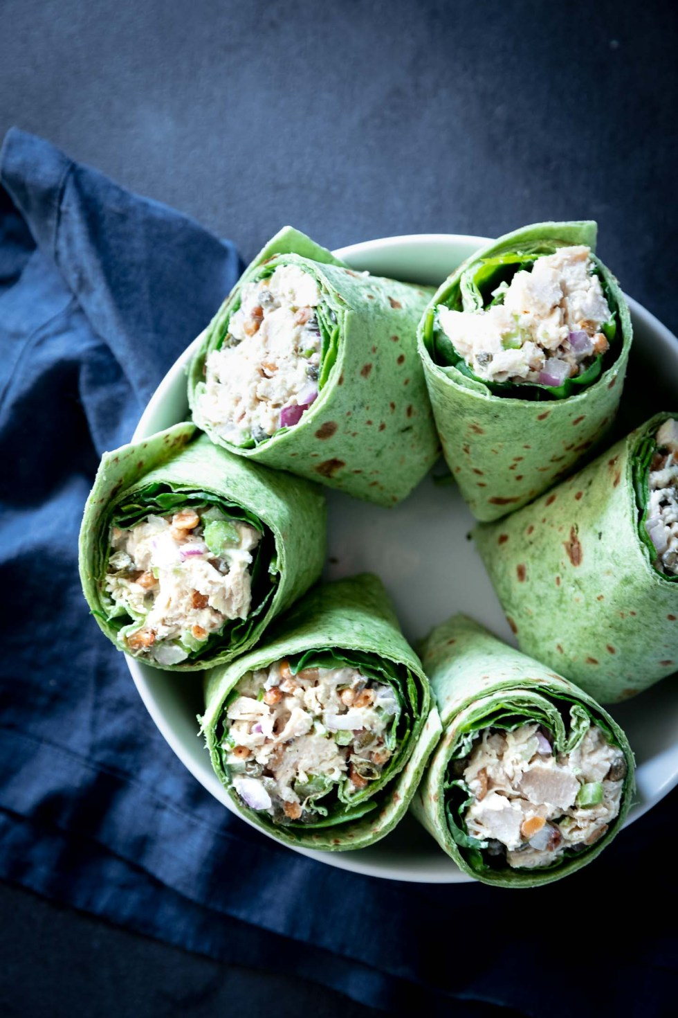 Overhead view of chicken salad wrap halves in a white bowl