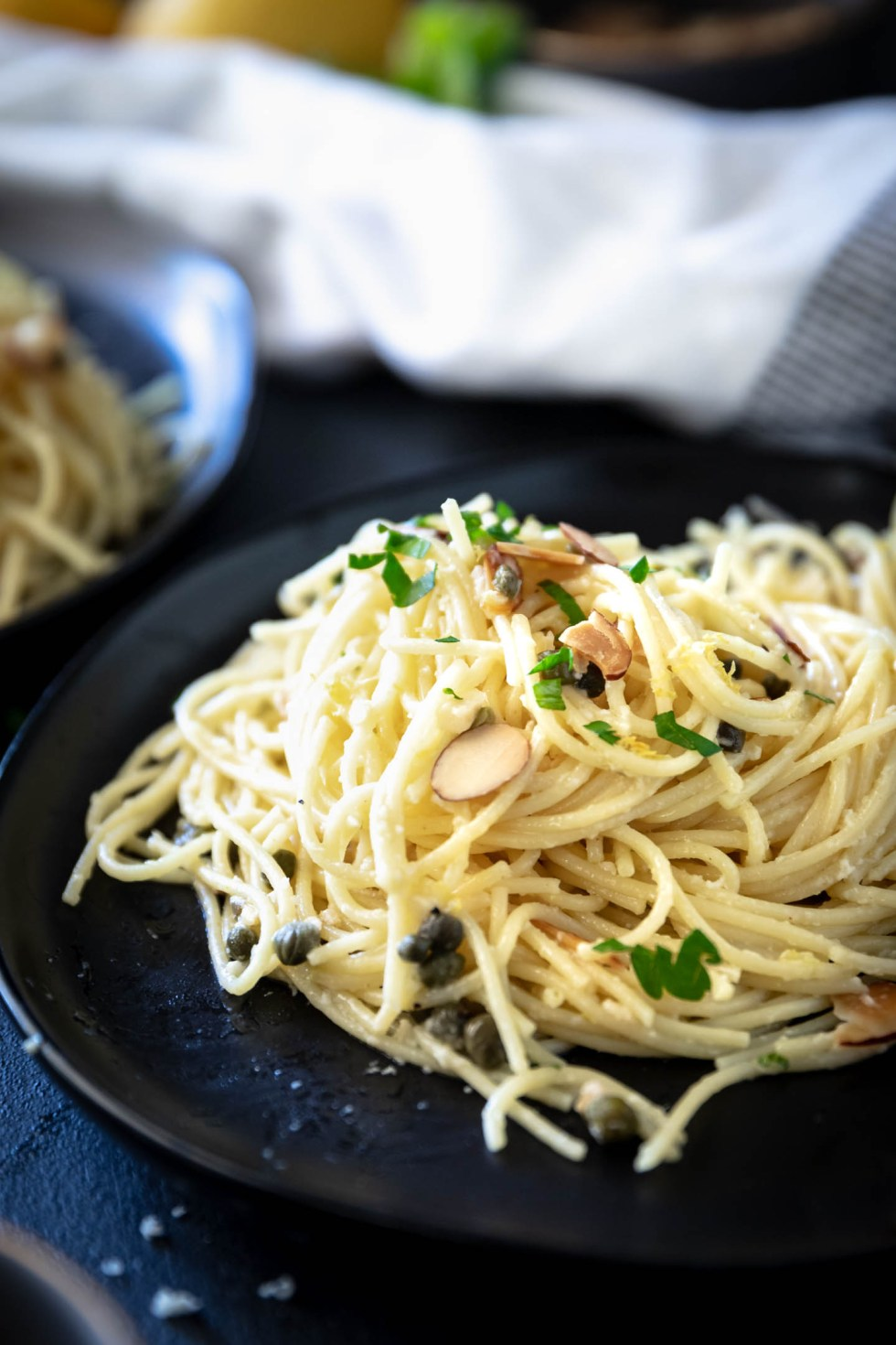 Closeup of a pile of lemon caper pasta on a black plate