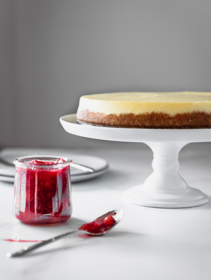 Table-level view of classic cheesecake on a white cake stand