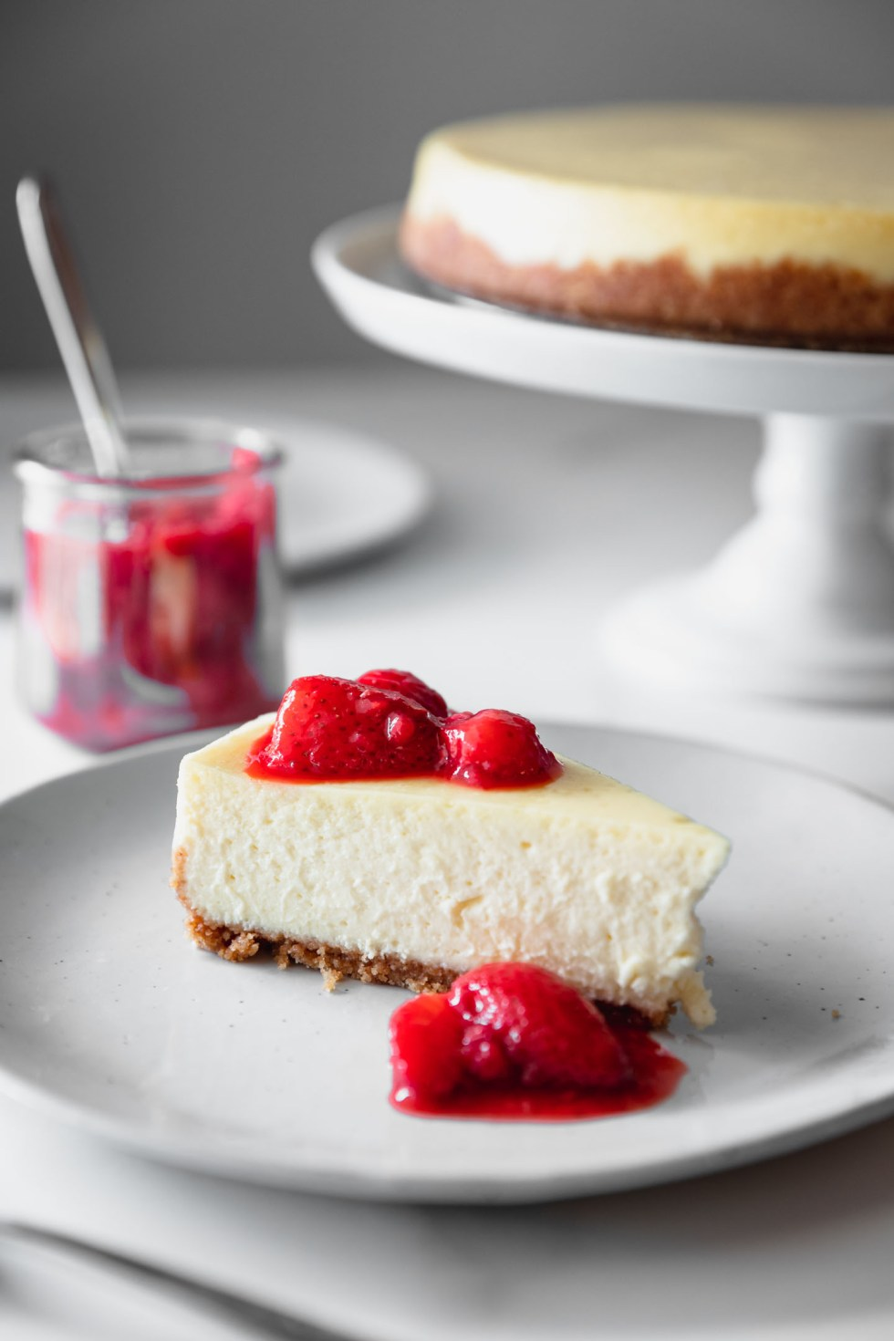 Closeup of new york style cheesecake with bright red berries on top