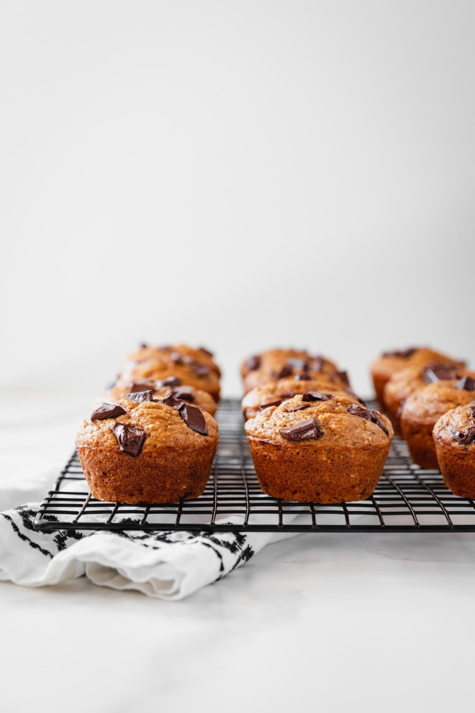 Front view of pumpkin muffins cooling on a rack