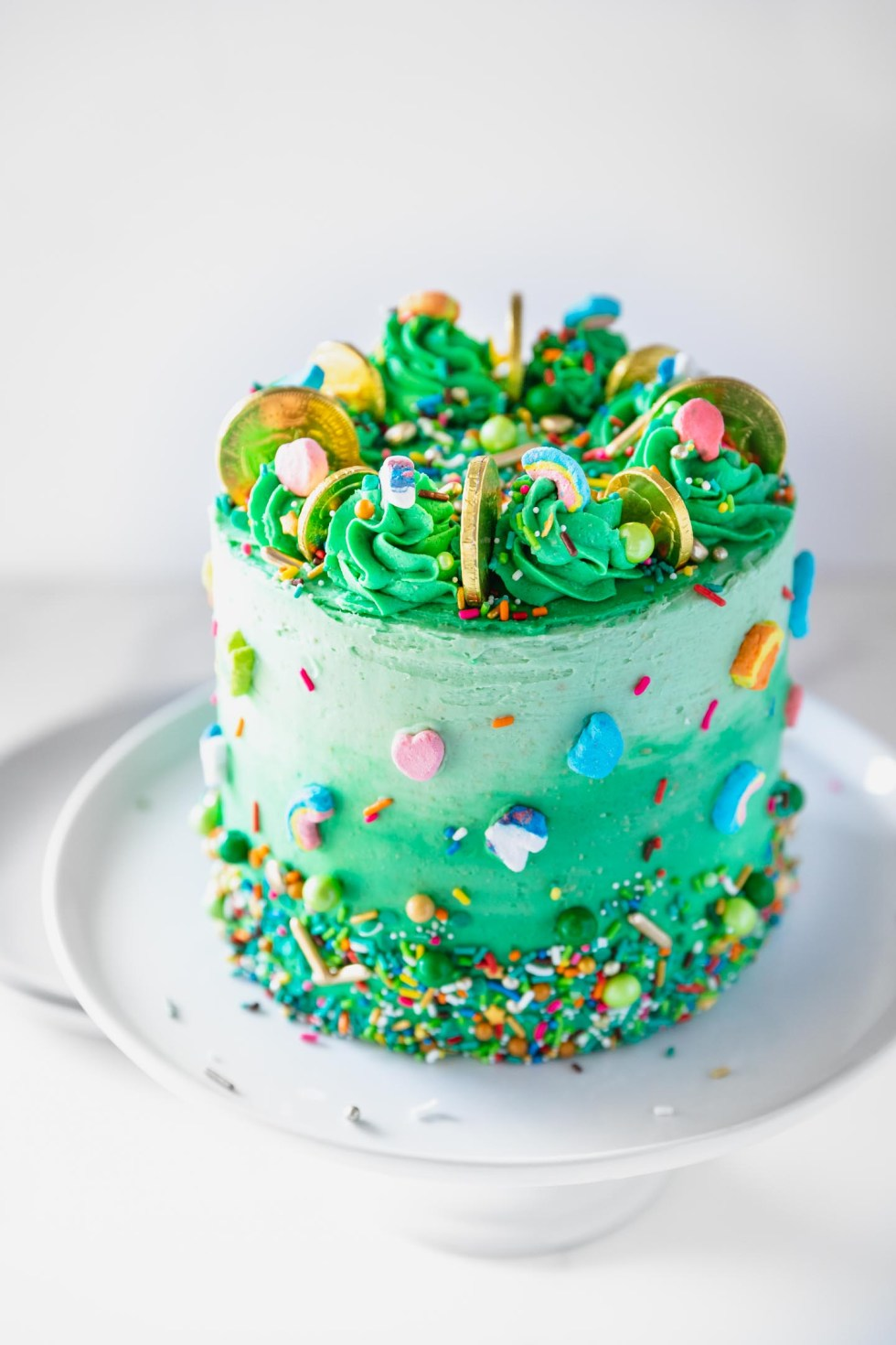 Front view of a green ombre cake with lucky charms and gold coins on top.