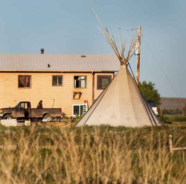 A teepee stands outside a home in Ethete, Wyoming
