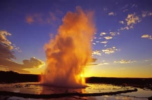 Great Fountain Geyser in Yellowstone National Park is lit by the sun, giving it an orange glow. (photo ©Leon Jenson — click to enlarge)