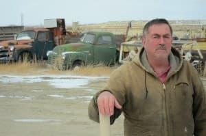 Jeffrey Locker stands next to a natural gas well behind his home near Pavillion.