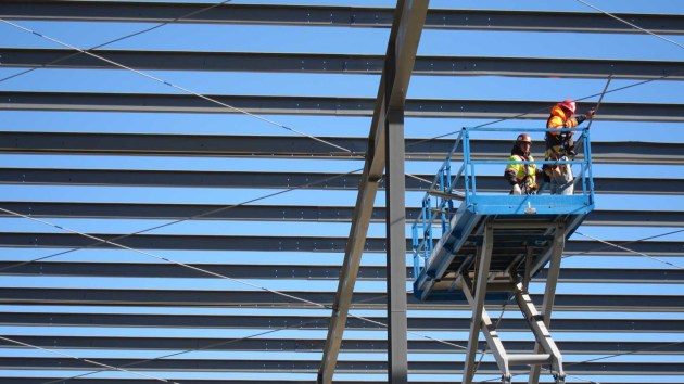 Workers use a scissor lift in the construction of a new Baker Hughes shop east of Casper. (Dustin Bleizeffer/WyoFile - click to enlarge)