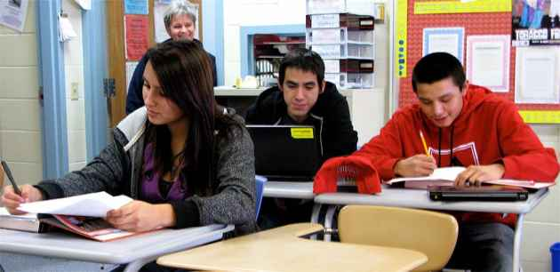 Delacina Chief Eagle, 15, a sophomore, studies world history during study hall at Wyoming Indian High School in Ethete. Edison Charley, 16, a freshman wearing red, and JJ Underwood, 17, a sophomore, work math problems. Superintendant Michelle Hoffman smiles and watches.