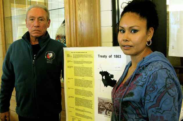 Orville St. Clair and Harmony Spoonhunter at the Eastern Shoshone Cultural Center in Fort Washakie, with an exhibit detailing the terms of the 1863 treaty between the Eastern Shoshone Tribe and the US government.