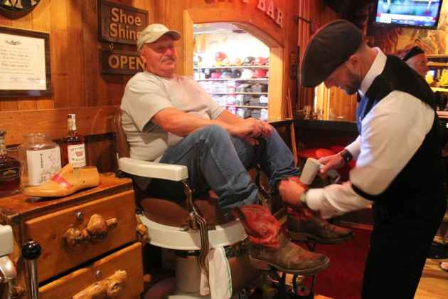Tim Tetley works on Gordon Little's boots at Tetley's shoe shine stand in the Cowboy Bar in Jackson. (WyoFile/Kelsey Dayton — click to enlarge)