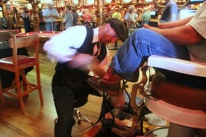 Tim Tetley works on shining a pair of boots at the Cowboy Bar in Jackson. (WyoFile/Kelsey Dayton — click to enlarge)